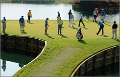 Players putt and survey the 17th green during a practice round for The Players Championship at the Stadium Course at TPC Sawgrass on Wednesday.