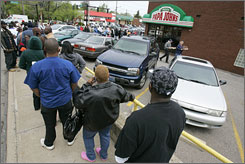 The line swings around the bend as a couple leave a Papa John's in University Heights, Ohio. The pizza restaurant made good on its apology to Cleveland Cavaliers fans by selling large pizzas for 23 cents each.
