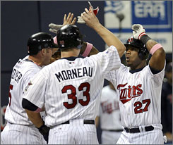 The Minnesota Twins' Craig Monroe, right, is congratulated at home plate by Michael Cuddyer, left, and Justin Morneau after Monroe hit one of the Twins' three home runs on the night in their 9-8 victory over Boston.