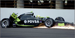 E.J. Viso's car sends up sparks as it scrapes along the third-turn wall during Friday practice at Indianapolis Motor Speedway.