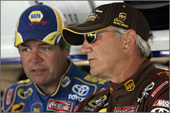 Dale Jarrett, right, talks things over with car owner Michael Waltrip during a break in Friday's practice.