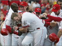 Slugger Adam Dunn crouches as he is mobbed by teammates after winning it for the Reds with a clutch three-run homer.