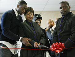 Miami Heat guard Dwyane Wade, left, accompanies his mother, Jolinda Wade, and pastor LaDell Jones in a ribbon-cutting ceremony at the Temple of Praise Church.