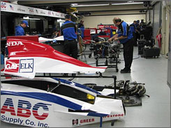 Crewmembers work their magic in the Indianapolis Motor Speedway garage area ahead of Sunday's 500-mile main event.