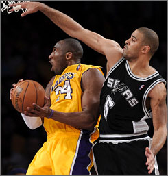 Lakers guard Kobe Bryant challenges the Spurs' Ime Udoka during the second half. Bryant scored 25 of his 27 points in the final 24 minutes as Los Angeles won the opening game of the Western Conference finals.