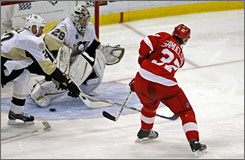 The Red Wings' Mikael Samuelsson, right, scores past Penguins defenseman Hal Gill, left, and goaltender Marc-Andre Fleury in the third period of Game 1 of the Stanley Cup finals in Detroit.