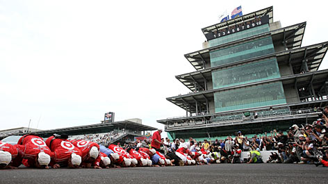 Scott Dixon's crew kisses the Indianapolis Motor Speedway's yard of bricks at the start-finish line after victory in the Indy 500.