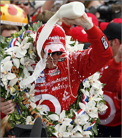 Scott Dixon pours the traditional winner's bottle of milk over his head as he enjoys the spoils at Indianapolis Motor Speedway.