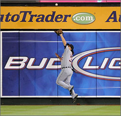 Tigers outfielder Magglio Ordonez makes a leaping catch at the wall on a ball hit by the Angels' Maicer Izturis in the ninth inning in Anaheim, Calif.