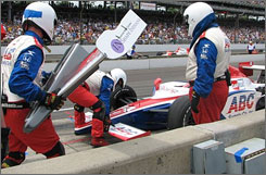 Crewmembers scramble to make one of two nose cone changes for the A.J. Foyt team during the 92nd running of the Indy 500.