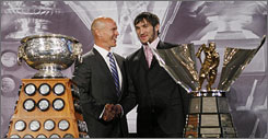 Washington Capitals forward Alex Ovechkin receives the Art Ross and Maurice Richard trophies from Mark Messier prior to Game 3 of the Stanley Cup Finals.