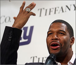 Giants defensive end Michael Strahan, showing off his new Super Bowl ring, would not address questions about whether he'll return for another season.