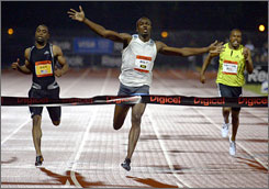 Usain Bolt, center, breaks the world record in the 100-meter dash, finishing in 9.72 seconds.
