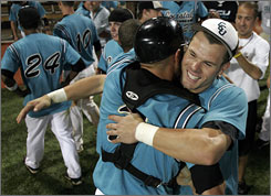 Coastal Carolina catcher Dock Doyle, left, and first baseman Adam Rice celebrate after the Chanticleers cut down East Carolina to win their NCAA regional last week. Next up for Coastal? A matchup with second-seeded North Carolina.