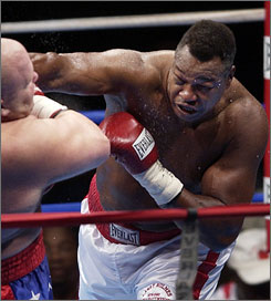 "Boxing great Larry Holmes takes care of business against opponent Eric ""Butterbean"" Esch in 2002. The fight was Holmes' last, and he won by unanimous decision after 10 rounds."