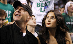Actor Bruce Willis, one of many stars in attendance, watches Game 1 of the NBA Finals with a companion.