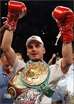 Kelly Pavlik poses with his WBO and WBC middleweight belts after easily dispatching challenger Gary Lockett in less than three rounds.