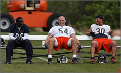 Linebacker Brian Urlacher, center, is unhappy with his contract, but he showed up at the Bears' minicamp.