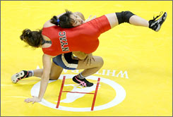 Clarissa Chun, in blue, lifts Mary Kelley in the challenger bracket championship match for the women's freestyle 48-kilogram division during the USA Olympic trials for wrestling and judo on Friday at the Thomas and Mack Center in Las Vegas.
