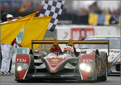 Tom Kristensen drives past the checkered flag to give Audi a victory in the 24 Hours of Le Mans. Kristensen wom with teammates Rinaldo Capello and Allan McNish.