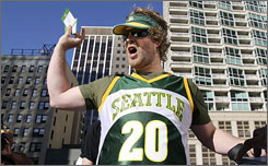 Sonics fan Jason Reid celebrates after receiving passes to the U.S. Courthouse in Seattle for Monday's proceedings.