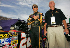 Driver Jamie McMurray stands with his father, Jim, before the start of the Lifelock 400 at Michigan International Speedway last weekend in Brooklyn, Mich.