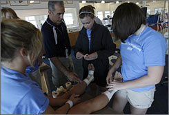 Eric Leighton, center, an athletic trainer with Children's Hospital, helps two girls during an Athletic Training workshop in Westerville, Ohio. The National Athletic Trainers' Association are pushing for more athletic trainers in schools, as they say only 42% of schools have access to them.