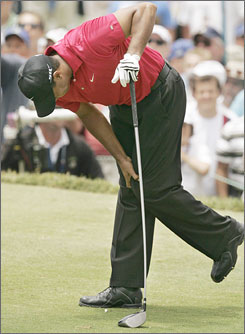 Tiger Woods clutches his left knee after hitting a shot during Sunday's round at the U.S. Open in San Diego.