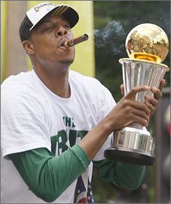 Celtics forward Paul Pierce shows off his MVP trophy from the NBA Finals during the team's victory parade in Boston on Thursday.