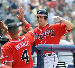 Mark Teixeira returns to the Braves dugout after hitting his third home run of the game, a two-run shot off Mariners reliever Ryan Rowland-Smith. It was Teixeira's second career three-homer game.