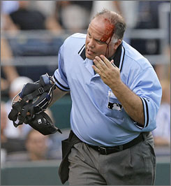 Home plate umpire Brian O'Nora runs toward the dugout after a broken bat from the Royals' Miguel Olivo struck him in the head in Kansas City.