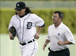 Detroit Tigers right fielder Magglio Ordonez, left, jogs off the field with trainer Kevin Rand. Ordonez left the game because of spasms in his side.
