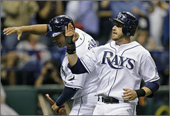 The Rays' Evan Longoria, right, and teammate Carlos Pena celebrate after scoring in Tampa Bay's 7-6 victory over the Red Sox in St. Petersburg, Fla.