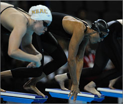 Dara Torres, right, gets out of the blocks slowly during her heat Thursday of the women's 100-meter freestyle. However, Torres defeated Katie Hoff, left, among others to win her heat in the third-fastest overall time.