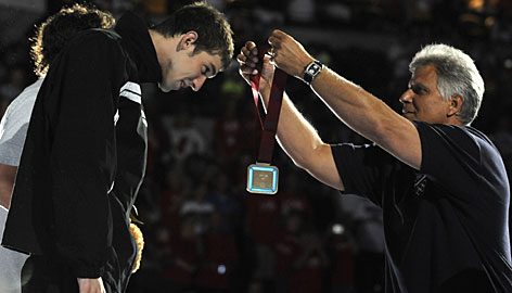 Swimming legend Mark Spitz awards Michael Phelps with the first-place medal for winning the men's 200-meter individual medley at the Olympic trials. Phelps broke his own world record in the event.
