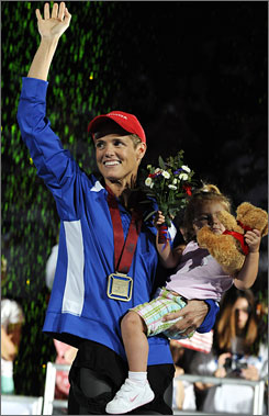 Dara Torres waves to the crowd while holding her daughter, Tessa, during the medals ceremony for the women's 100-meter freestyle at the Olympic trials. Torres, 41, won the race and qualified for her fifth Olympics.