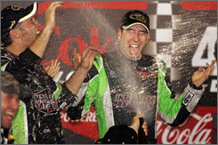 Kyle Busch gets a champagne shower in victory lane after winning the Coke Zero 400 Saturday night at Daytona International Speedway.