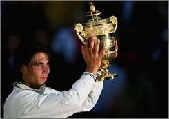 Rafael Nadal of Spain celebrates with the championship trophy after winning the men's singles finals against Roger Federer in London.