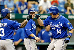 Kansas City catcher John Buck, right, plated teammates Esteban German, left, and Ross Gload with his three-run, 10th-inning home run as the Royals defeated the Tampa Bay Rays 7-4.