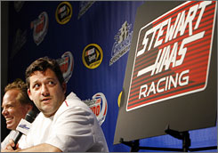 Tony Stewart, with new co-owner Joe Custer, looks at a sign of things to come as he breaks the expected news at Chicagoland Speedway, announcing the formation of Stewart Haas Racing.
