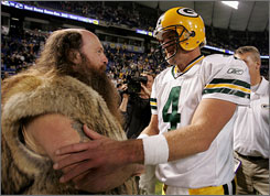 The Green Bay Packers allege that the contact with the Minnesota Vikings may be motivating Brett Favre, seen here with the Vikings' mascot in 2006, to come out of retirement.