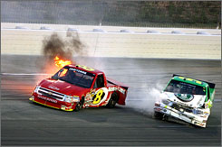 Chad McCumbee's No. 8 Chevrolet, left, catches fire after colliding with the No. 9 Toyota, right, of driver Justin Marks, between turns three and four during the Built Ford Tough 225 at Kentucky Speedway. Neither driver was injured.