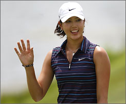 Michelle Wie waves to fans upon reaching the 18th green during the third round of the State Farm Classic on Saturday. Minutes after finishing her round in second place, Wie was informed she had been disqualified from the event after failing to sign her scorecard on Friday.