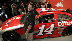 Tony Stewart offers a wink during a news conference to show off his new ride for 2009.
