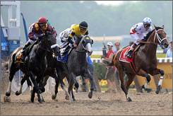 Macho Again, center, ridden by Garrett Gomez and Big Brown, right, ridden by Kent Desormeaux race at the Belmont Stakes in June. The horses may be headed for a rematch in the $1 million Travers on Aug. 23.