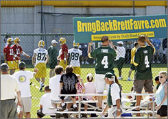 Packers quarterback Aaron Rodgers (12) practices with his teammates while a group of Green Bay fans show their support for Brett Favre at a Friday workout.