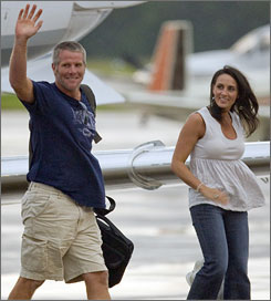 Brett Favre, with his wife Deanna, waves to fans assembled at the airport after arriving in Green Bay on Sunday night.