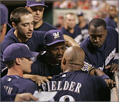 The Milwaukee Brewers' Prince Fielder is held back by his teammates after he had an altercation with starting pitcher Manny Parra in the dugout during Monday's 6-3 loss to the Cincinnati Reds.