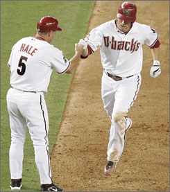 Arizona Diamondbacks Mark Reynolds, right, is congratulated by third base coach Chip Hale after hitting a solo home run against the  Pittsburgh Pirates during the fifth inning. Arizona beat Pittsburgh 13-7 Monday night.