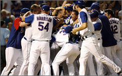 The Texas Rangers celebrate after Marlon Byrd hits a walk-off grand slam in the bottom of the ninth inning, giving the Rangers a 9-5 win Monday vs. the New York Yankees.